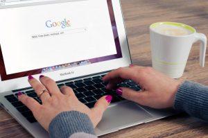 Image d'une femme surfant sur Google avec un Mac Book - Site web